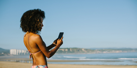 Banner of young beautiful black woman texting on cell phone at the beach on summer or spring vacation. Mobile communication on travel concept. San Juan de Nieva, Asturias, Spain. Banco de Imagens