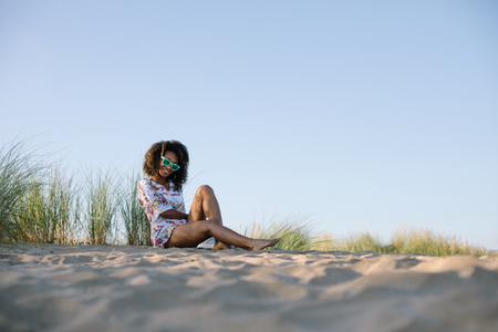 Young beautiful black woman relaxing at the beach on summer or spring vacation. San Juan de Nieva, Asturias, Spain. Banco de Imagens