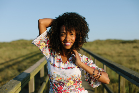 Joyful happy woman on spring or summer outdoor relaxing leisure. Afro hair young black female.