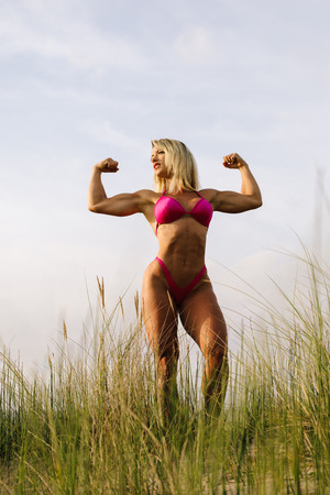Strong fitness woman on summer outdoor. Bikini fit muscular female body. Beautiful bodybuilder flexing strong arms. Stock Photo