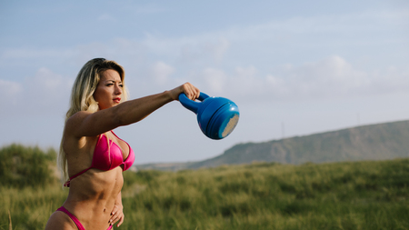 Fitness woman on summer outdoor workout. Bikini fit muscular female body doing kettlebell swing exercise. Banco de Imagens