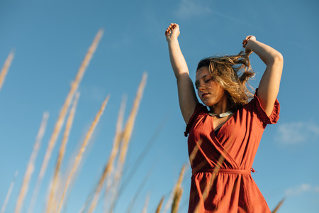 Summer freedom and relaxing leisure. Young relaxed woman raising arms to feel the breeze at the beach against blue clear sky.