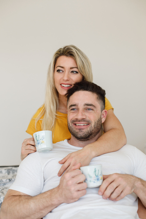 Lovely young casual couple embracing and drinking coffee at home. Love and relationship tranquility concept. Stock Photo