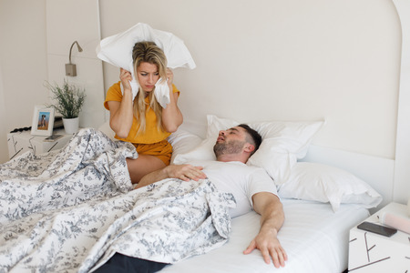 Woman covering her ears with the pillow because of the loud snoring of her partner. Bed couple relationship problems. Foto de archivo