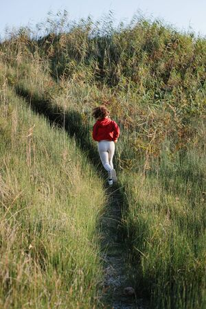 Back view of young woman on cross country running training. Stock fotó
