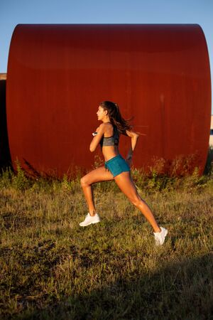 Side view of fit female athlete running on urban industrial zone. Young woman exercising outdoor. Stock Photo