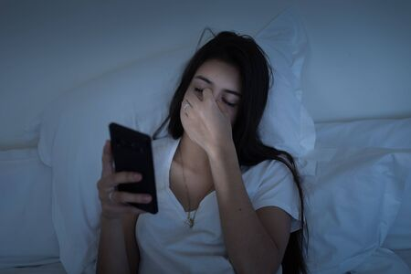 Eye fatigue due to blue light from smartphone screen. Millennial young sleepy girl using mobile phone in bed at night. Cellphone addition and tech sleep disorders concept. Banque d'images - 131790947