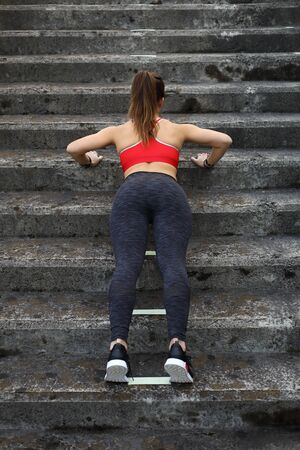 Back view urban fitness woman workout doing incline push ups on stairs. Motivated female athlete training hard. Stock Photo