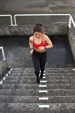 Sporty young woman on fitness and running urban workout climbing stairs.