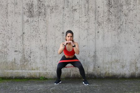 Urban fitness outdoor workout with resistance band. Young fit woman doing banded Step-Outs.