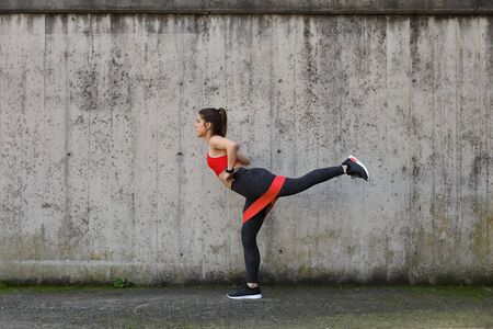 Urban fitness outdoor workout. Fit athlete exercising with resistance band to strengthen the glutes. Stock Photo