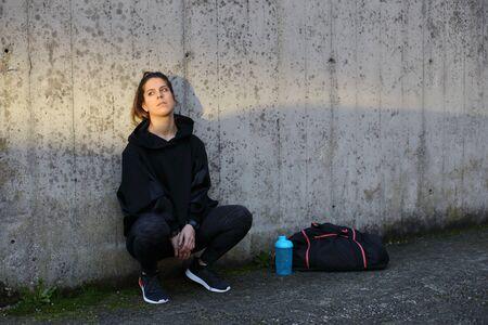 Allenamento mattutino all'aperto di fitness urbano. Giovane donna sportiva che prende un periodo di riposo. Stile di vita sano nel concetto di città.