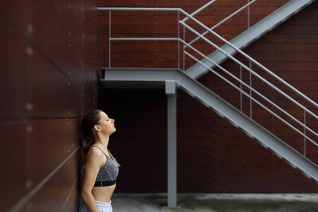 Relaxed sporty woman taking a rest for breathing after urban fitness workout. Fitness lifestyle success concept. 写真素材