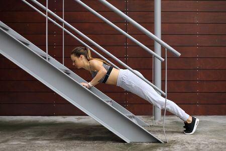 Fit young woman doing incline push ups exercise using urban stairs. City outdoor fitness workout.
