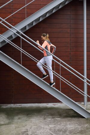 Sporty young woman on fitness and running urban workout climbing stairs for hiit cardio training. Stock fotó