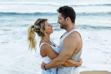 Juguetón joven pareja de enamorados abrazándose y mirando el uno al otro en la playa en vacaciones de verano.