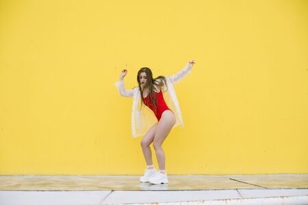 Urban hiphop style girl dancing in the street against yellow wall. Banque d'images - 133350561