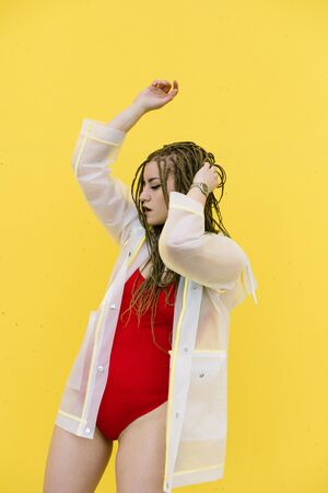 Urban hiphop style girl dancing in the street against yellow wall. Banque d'images - 133350565