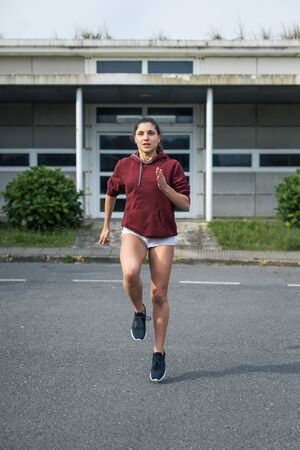 Female athlete running in place. Sporty young woman training on asphalt. Stock Photo