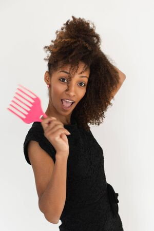 Pretty afro hairstyle woman using comb for untangle her curly hair. Black female beauty and style tips concept. Stock fotó