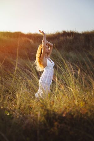 Blissful woman relaxing and feeling the breeze in summer sunset. Freedom and relax concept.