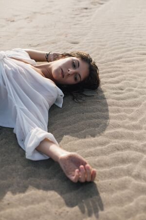 Young woman relaxing at the beach lying on the sand. Summer vacation relax and leisure concept.