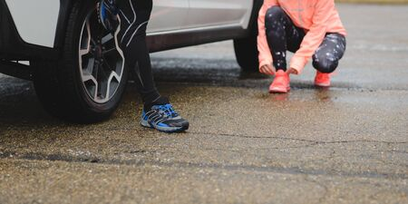 Detail of couple of runners on sport winter car trip getting ready for running.