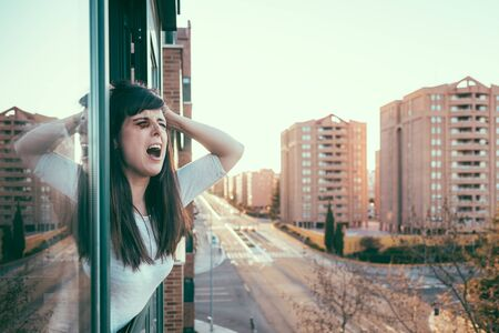 Despair woman with black eye crying desperately asking for help peeking out the window.