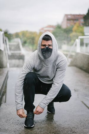 Sporty man wearing facial mask for protection against coronavirus and pollution during winter running