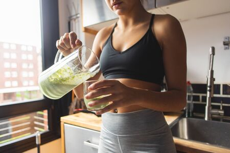 Sporty woman serving a green detox smoothie for breakfast in the kitchen. Stockfoto
