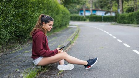 Sporty young woman taking a running rest for checking workout goals on smartphone app.
