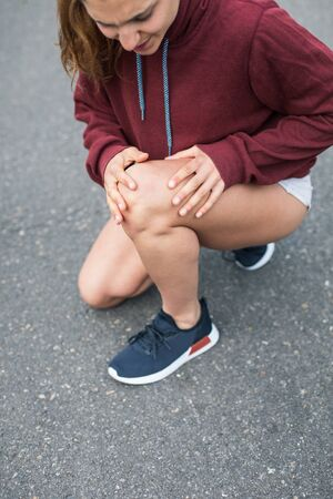 Detail of female athlete suffering from running knee painful injury.