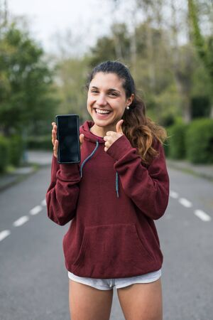 Successful young female athlete doing thumbs up gesture and showing phone screen. Stockfoto