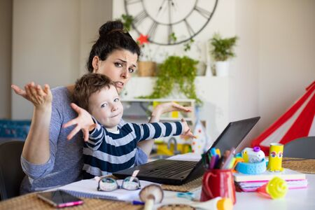 Busy mother working from home and taking care of her child. Stockfoto