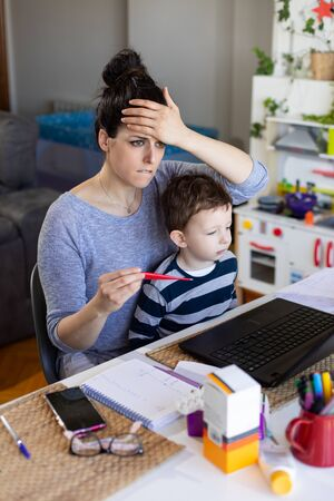 Sick mother telecommuting and caring for her child. Stockfoto