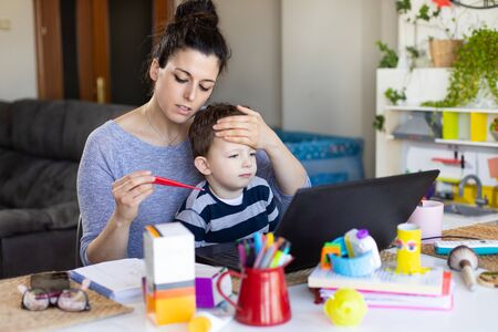Busy mother telecommuting and caring for her sick child.