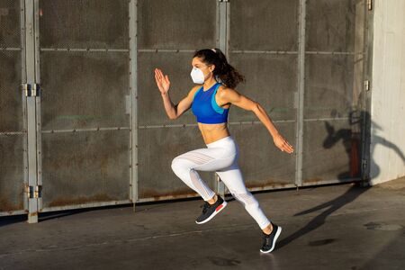 Side view of young female athlete running fast outside wearing face mask in the city.