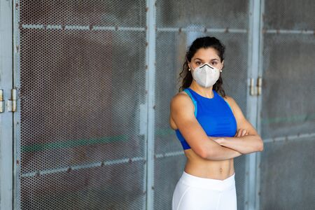 Confident young fit female athlete wearing face mask for protection against Covid-19.