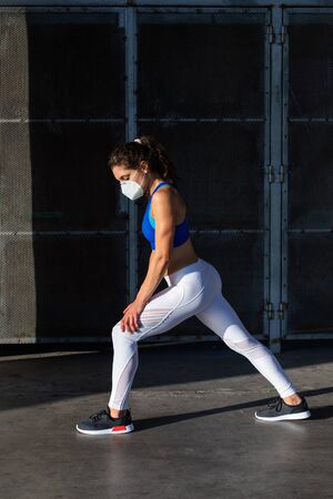 Side view of young female athlete  wearing face mask while training outside in the city.