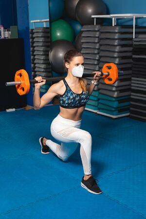 Young fit woman doing lunges at the gym wearing n95 face mask. Stockfoto