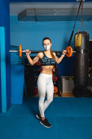 Young fit woman with n95 face mask  exercising at the gym with weights.