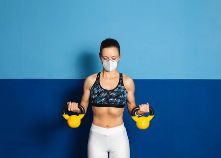 Young fit woman with n95 face mask  doing biceps exercise at the gym with kettle bells.