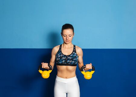 Young fit woman doing biceps exersice at the gym with kettlebells. Fitness strength workout.