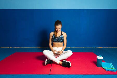 Fit sporty young woman at the gym taking a rest for using smartphone fitness app and ckecking workout goals.
