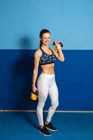 Young healthy fit woman posing with kettlebells at the gym. Fitness lifestyle success.