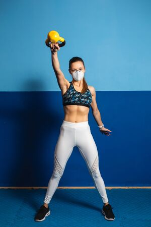 Young fit woman with n96 face mask  doing shoulder exercise at the gym with kettlebells.