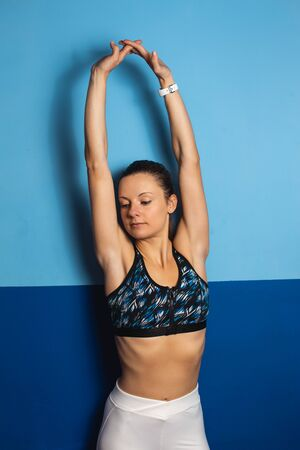 Young fit woman doing arms stretching exercise at the gym. Stockfoto