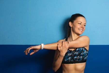 Young cheerful fit woman doing shoulder stretching exercise at the gym.
