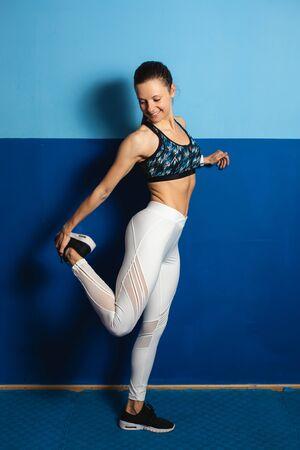 Fit young healthy woman stretching quadriceps.