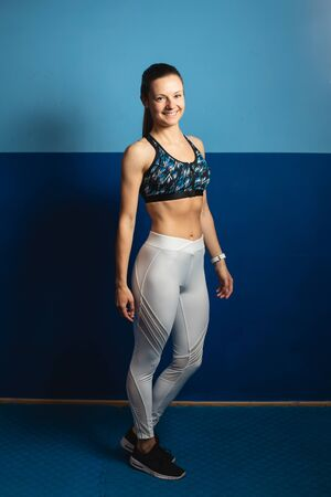 Young healthy fit woman full length portrait at the gym.